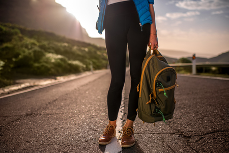 without legs: Female traveler holding backpack standing on the mountain road. Medium plan view without face focused on legs