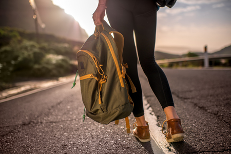 without legs: Female hitchhiker walking with backpack on the mountain road. Medium plan rear view without face focused on legs Stock Photo