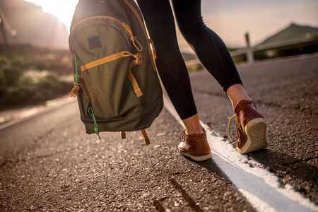mujer que viajaba caminar con la mochila en la carretera de montaña. vista trasera más cercana sin cara que está enfocada en las piernas y una mochila Foto de archivo