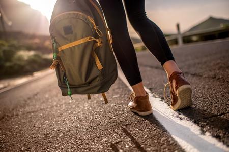 Vrouwelijke reiziger wandelen met rugzak op de berg weg. Close-up zicht naar achteren zonder gezicht gericht op de benen en rugzak Stockfoto