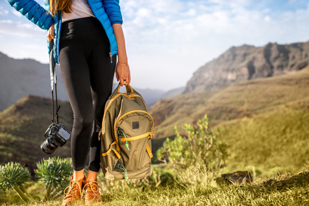 without legs: Female traveler holding photocamera and backpack standing on the beautiful mountains background. Medium plan view without face focused on legs