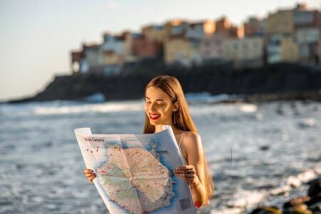 holiday trip: Young female traveler with tourist map on the beach near the old town El Roque on Canarian islands Stock Photo