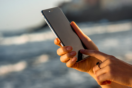 Gran Canaria, Spain - December 13, 2015: Female hands holding new iPhone 6s Space Gray on the blurred sea background. iPhone 6 was created and developed by the Apple inc.