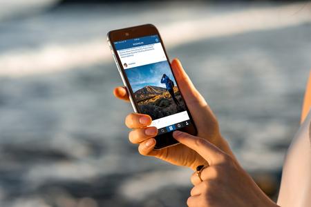 Gran Canaria, Spanje - 13 december 2015: Vrouw die op Instagram nieuws uit RossHelen rekening met nieuwe iPhone 6s Space Gray op de onscherpe achtergrond van de zee. iPhone 6 werd gecreëerd en ontwikkeld door Apple inc. Instagram is een populaire online sociale netwerken