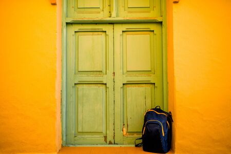 back pack: Blue back pack near the green door and yellow wall in Aguimes town on Gran Canaris island