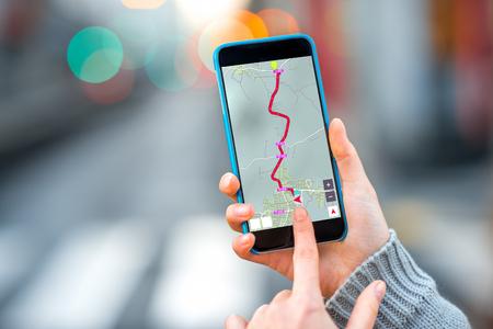 Het wijfje dient de smartphone van de sweaterholding met gps navigatieprogramma op de vage grijze stadsachtergrond in Stockfoto