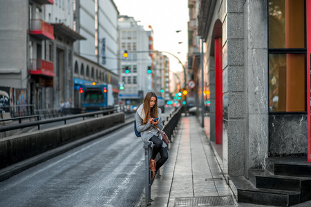 sweater girl: Young woman in casual gray clothes using smartphone sitting near the street on the gray city background