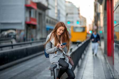 Young woman in casual gray clothes using smartphone sitting near the street on the gray city background Banco de Imagens - 50017075