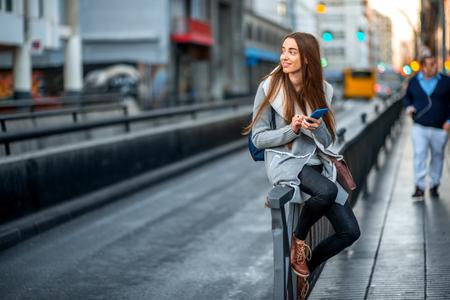 회색 도시 배경에 거리 근처에 앉아 스마트 폰을 사용하여 캐주얼 회색 옷에 젊은 여자 스톡 콘텐츠
