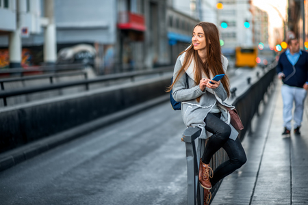urban style: Young woman in casual gray clothes using smartphone sitting near the street on the gray city background