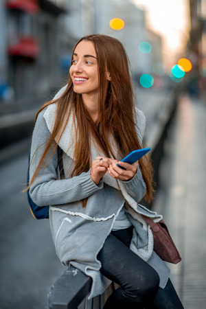 long hair: Young woman in casual gray clothes using smartphone sitting near the street on the gray city background