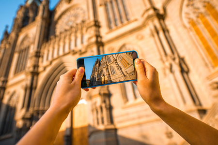 northern spain: Female tourist photographing with smartphone Church of San Juan Bautista in Arucas on nothern part of Gran Canaria island. Stock Photo