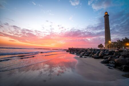 beaches of spain: Beautiful sunset view on the beach with lighthouse in Maspalomas city on Gran Canaria island Stock Photo