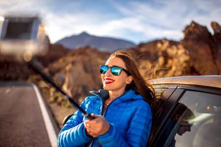 long hair: Young woman in blue jacket taking selfie photo with small action camera near the car on the mountain road with volcano on background