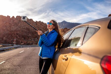 long: Young woman in blue jacket taking selfie photo with small action camera near the car on the mountain road with volcano on background