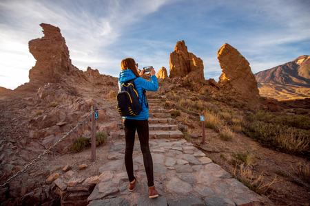 desierto: viajero femenino joven que fotograf�a con la belleza del paisaje rocoso de tel�fonos inteligentes en el parque del Teide en la isla de Tenerife