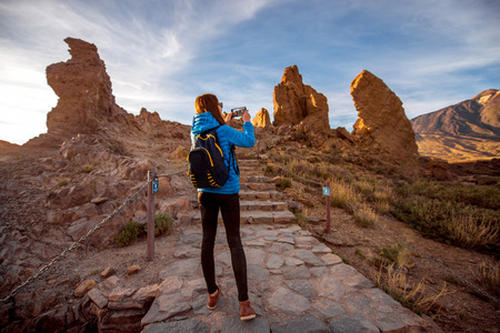 desert island: Young female traveler photographing with smartphone beautiful rocky landscape in Teide park on Tenerife island Stock Photo