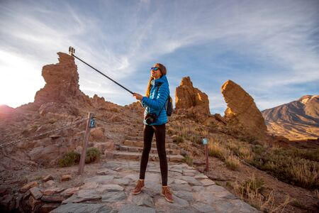 island: Young female traveler making selfie with small action camera on a stick on the beautiful rocky background in Teide park on Tenerife island