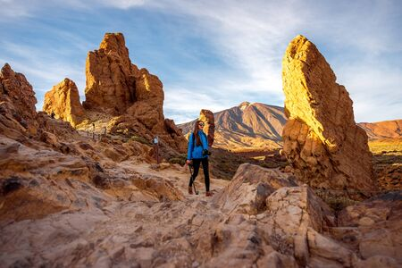 island: Young female traveler walking on the beautiful rocky landscape in Teide park on Tenerife island