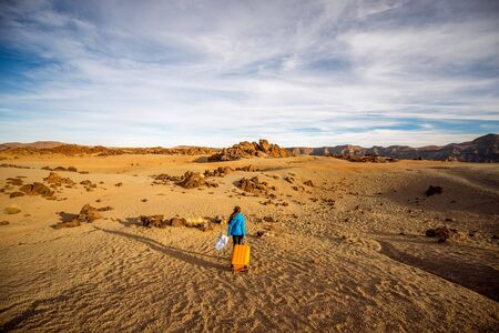 desert: Young female traveler walking with yellow suitcase on the rocky desert in teide park on Tenerife island. Wide angle view with copy space