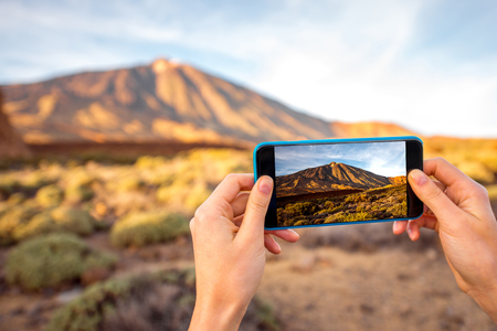 island: Female hands photographing with smartphone beautiful landscape with volcano in Teide park on Tenerife island