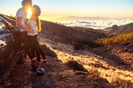 pareja besandose: pareja de jóvenes vestidos igual en la camiseta blanca y un sombrero que abarca cerca del coche en la carretera en la puesta del sol. Foto de archivo