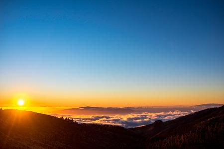 テネリフェ島の夕日に雲の上からラ ・ ゴメラ島の美しい風景を眺める。 写真素材