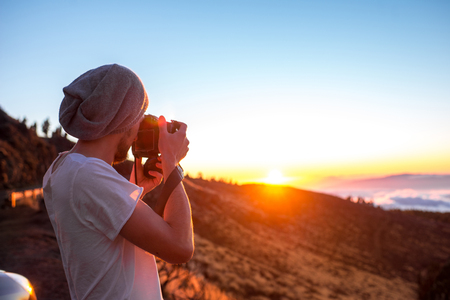 Man photographing beautiful landscape above the clouds on the sunset Stock Photo - 51510899