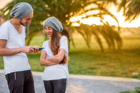 alike: Young modern couple dressed alike in white t-shirt and hat using smart phone in the park with palms on background in the morning