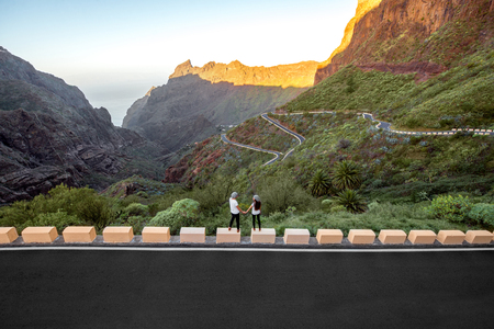 highway love: Beautiful rocky landscape with mountain road and carefree couple standing on the roadside. Wide angle shot with copy space