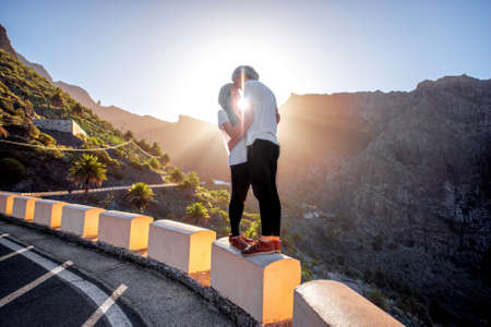 highway love: Young couple in white t-shirts embracing on the roadside on the mountain road on the sunrise Stock Photo