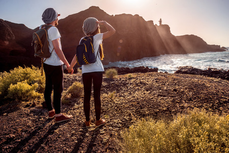 people travelling: Young couple dressed alike with backpacks traveling island near the rocky ocean coast with lighthouse on the sunset