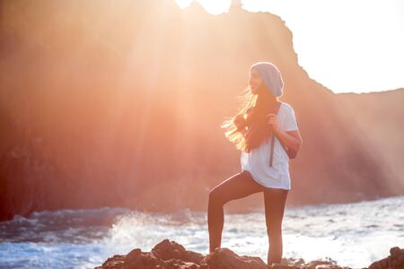 people travelling: Young woman with backpack standing on the rocky ocean coast on the sunset. Stock Photo