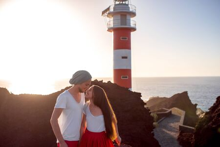 femme romantique: Romantic couple dressed in white and red standing together near the lighthouse on the sunset