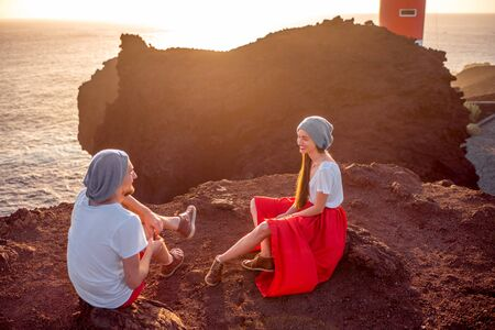 sitting on the ground: Romantic couple dressed in white and red sitting together on the ground near the lighthouse on the sunset. Couple enjoying summer vacation