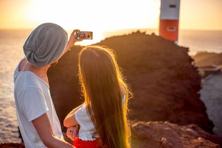 femme romantique: Romantic couple dressed in white and red taking selfie photo with rocks, lighthouse and oecan on the background on the sunset. Enjoying summer vacation concept