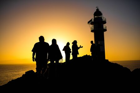contrasted: Silhouettes of people on the rocky coastline near the lighthouse. Deep contrasted yellow and black image