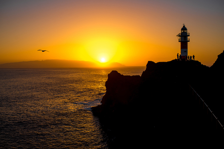 contrasted: Rocky coastline with lighthouse on the sunset. Deep contrasted yellow and black image Stock Photo