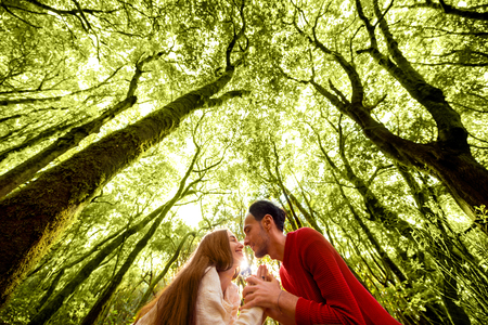 romantic heart: Young and lovely couple dressed in sweaters kissing in the green forest with beautiful trees covered with moss on the background. Wide angle image with copy space