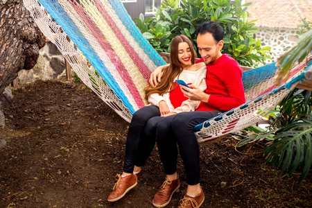 people relax: Young couple in sweaters using smart phone sitting together on the hammock in the garden