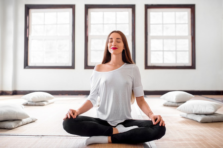 yoga pillows: Young and positive woman in white t-shirt and black leggings practicing yoga in the bright interior with big windows. Stock Photo