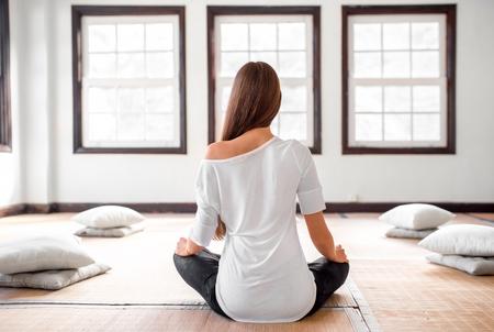흰색 t- 셔츠와 큰 창문 밝은 인테리어에 요가 연습 검은 레깅스에 젊고 긍정적 인 여자. 스톡 콘텐츠