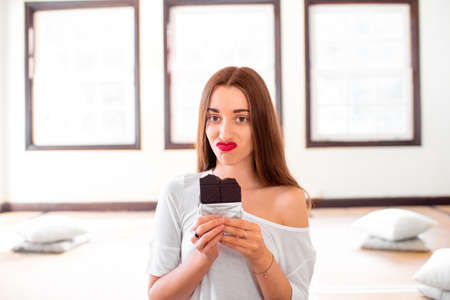 Woman with disappointed emotions thinking about sweet food worrying about calories and weight sitting in the sport gym