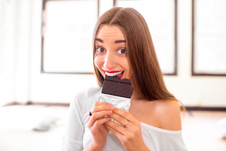 yoga pillows: Young and smiling woman eating black chocolate without worrying about calories and weight sitting in the gym