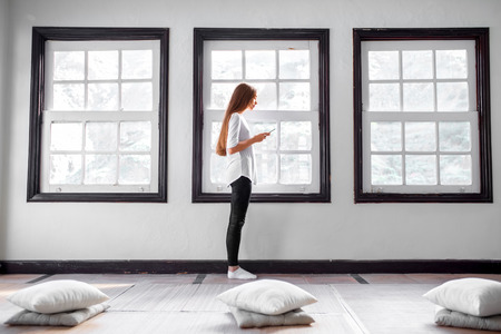 yoga pillows: Young  woman using phone standing near the window in the sport gym after practising yoga