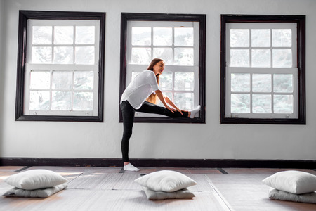 yoga pillows: Young and sporty woman streching near the window in the bright gym interior