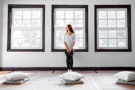 yoga pillows: Young and sporty woman sitting on the window in the bright gym interior Stock Photo