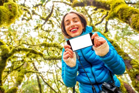 copy paste: Young woman in blue jacket showing smart phone with white screen to copy paste on the beautiful evergreen forest background