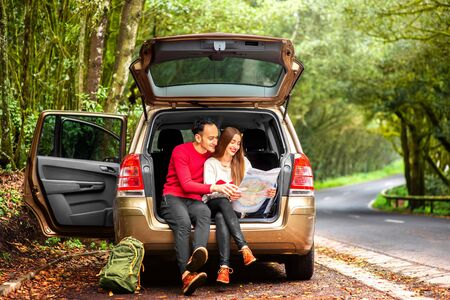car trunk: Young couple in sweaters sitting in the car trunk with paper map on the roadside in the forest.