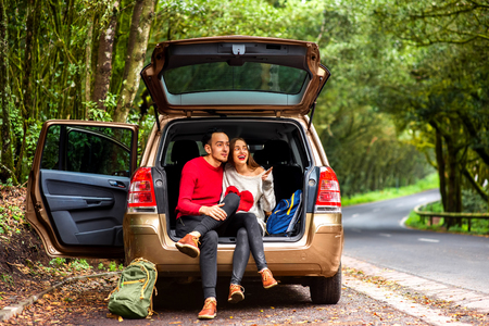 car trunk: Young couple in sweaters sitting in the car trunk with backpacks on the roadside in the forest.